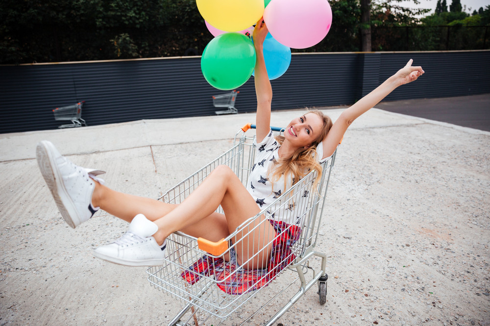 Beautiful happy girl sitting in shopping cart and holding color balloons outdoors