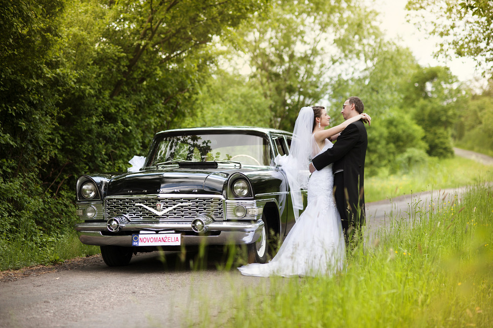 Beautiful happy young bride and groom posing by the retro car. Outdoor wedding portrait.