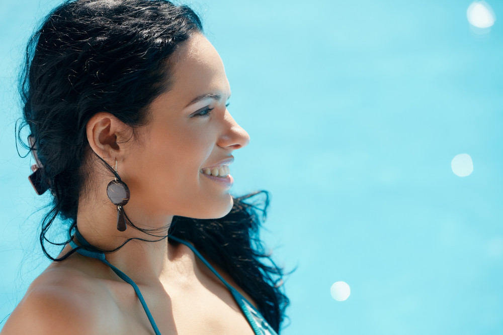 Beautiful happy young hispanic woman smiling and relaxing near resort swimming pool. Horizontal shape, side view, copy space