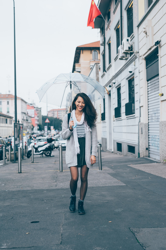 Beautiful long straight hair asian woman walking outdoor in the city holding an umbrella in a rainy day, smiling - happiness, joy, carefree concept