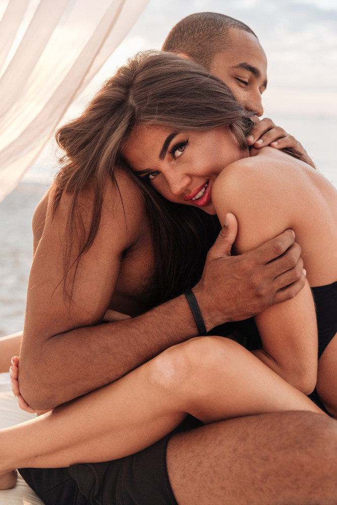 Beautiful loving young couple sitting and embracing on the beach