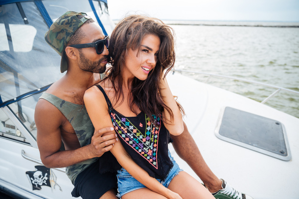 Beautiful loving young couple smiling and embracing on yacht