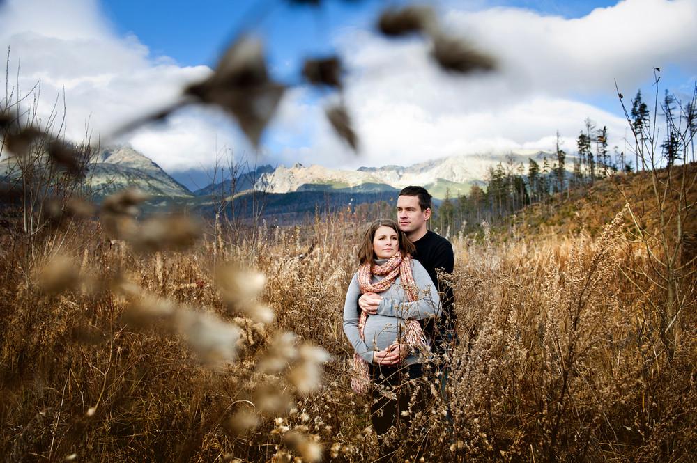 Beautiful outdoor pregnant couple portrait in autumn nature