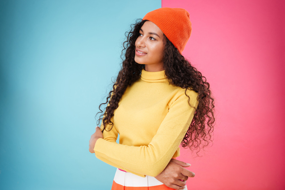 Beautiful pensive african young woman in hat standing and thinking over colorful background