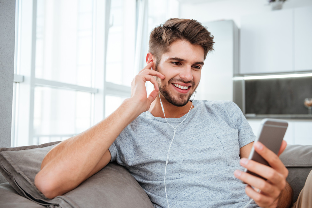 Beautiful portrait of young man listening to music while lies on sofa and chatting.