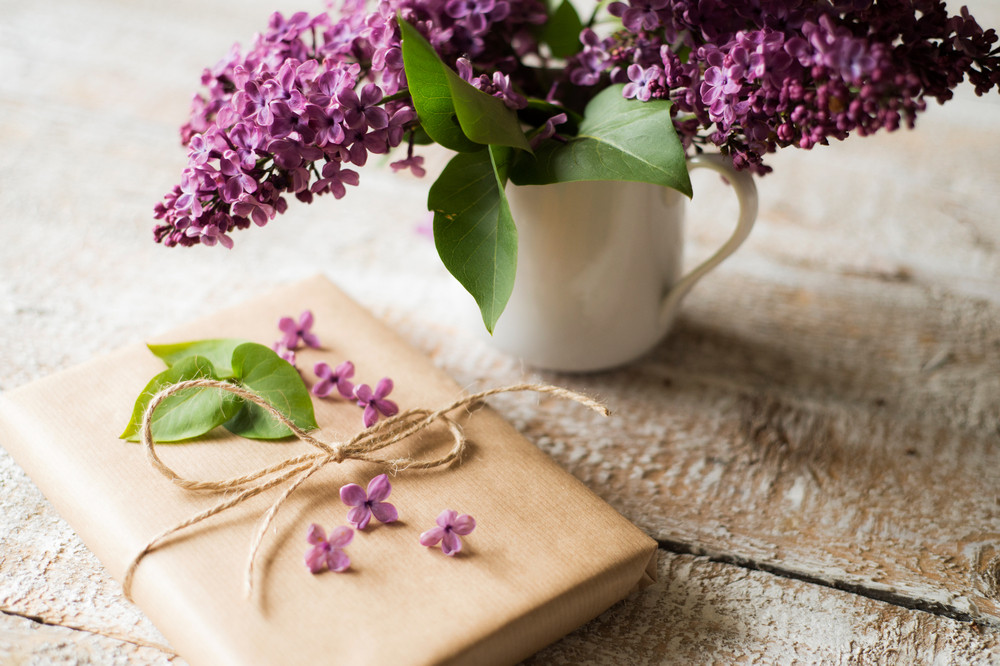 Beautiful purple lilac bouquet in vase laid on table and present wrapped in brown paper. Studio shot on white wooden background.