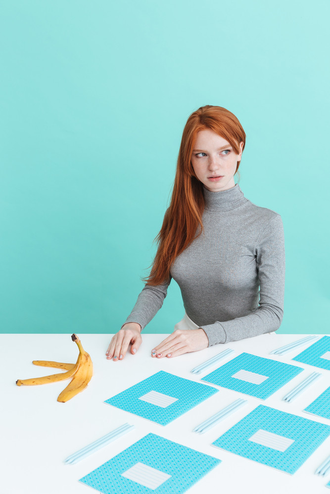 Beautiful redhead young woman sitting at the table with copybooks, pens and