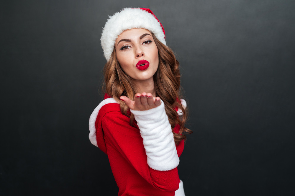 Beautiful santa's helper sending us an air kiss. posing standing sideways over black background