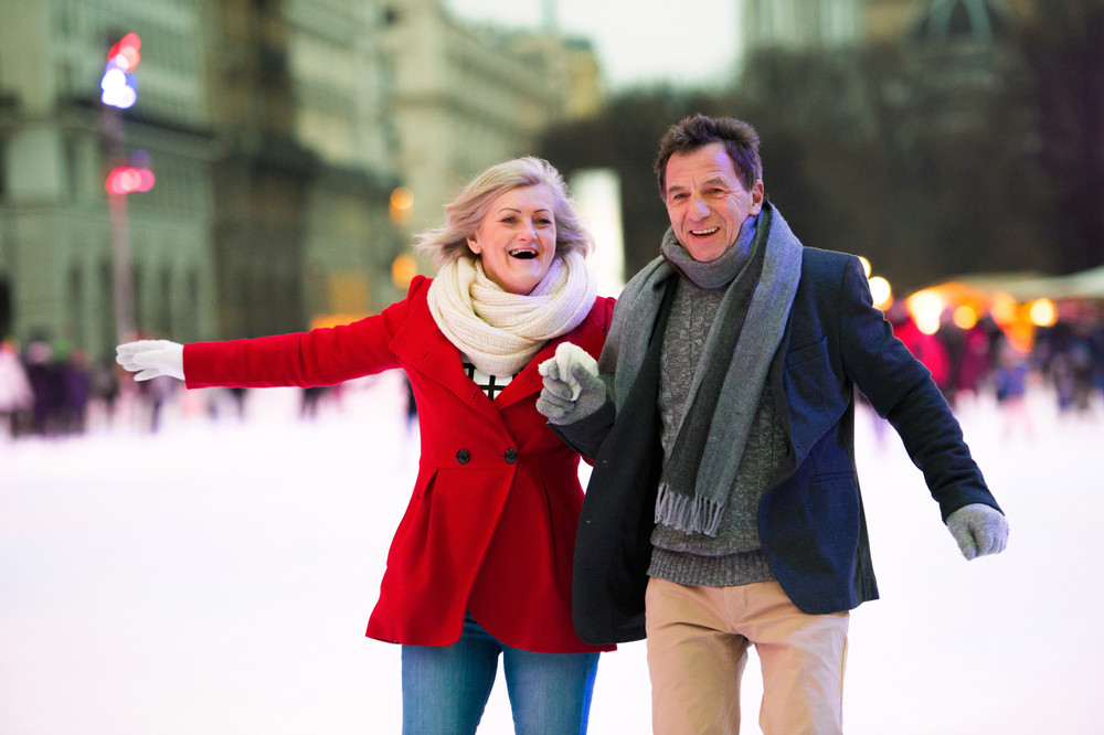 Beautiful senior couple ice skating in historical centre of the city of Vienna, Austria. Winter.