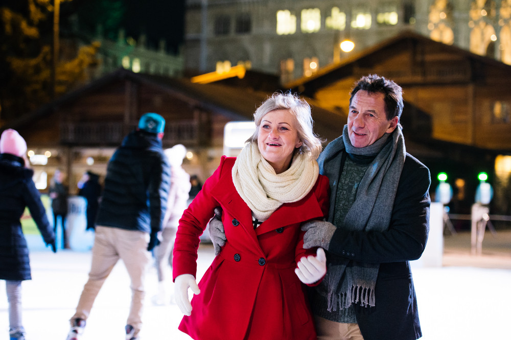 Beautiful senior couple ice skating in the evening in historical centre of the city of Vienna, Austria. Winter.