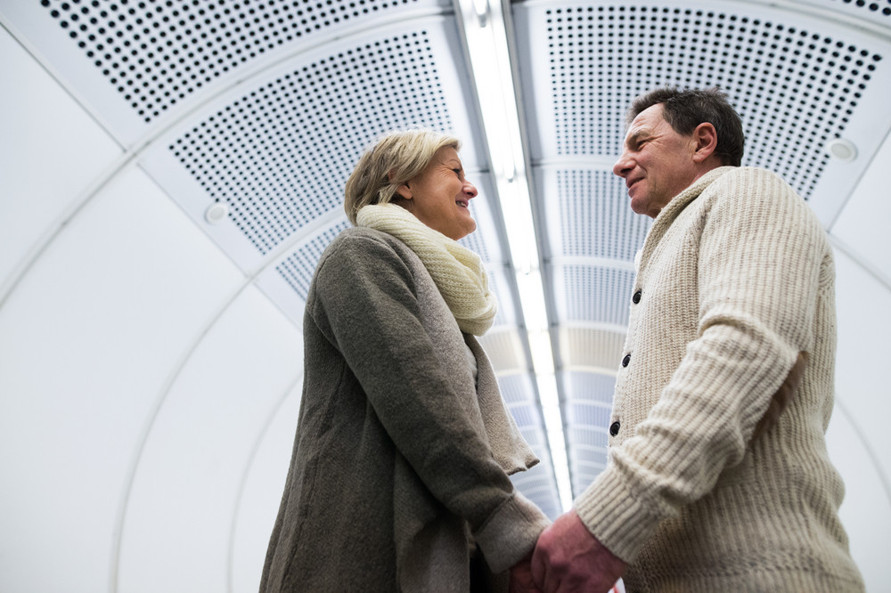 Beautiful senior couple in the hallway of subway in Vienna, facing each other, holding hands
