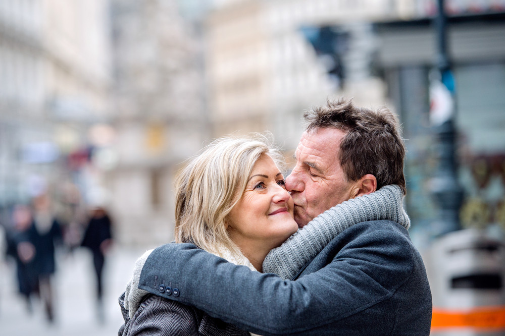 Beautiful senior couple on a walk in historical centre of the city of Vienna, Austria. Man kissing woman on cheek. Winter.