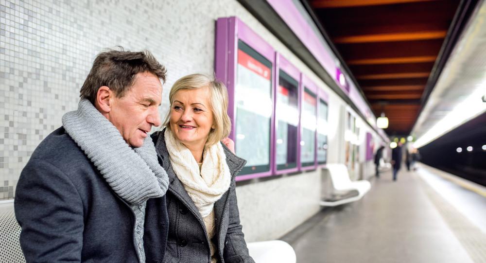 Beautiful senior couple sitting at the underground platform, waiting
