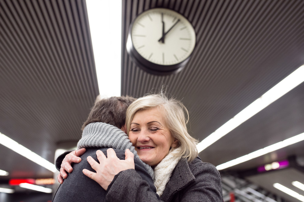 Beautiful senior couple standing at the underground platform, hugging. Welcoming or saying good bye. Five past twelve.