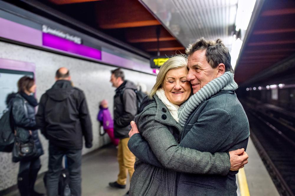 Beautiful senior couple standing at the underground platform, waiting, hugging