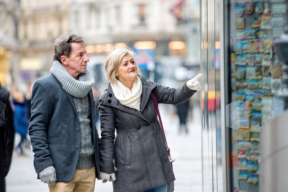 Beautiful senior couple window shopping in historical centre of the city of Vienna, Austria. Winter. Woman pointing at somoething with finger.