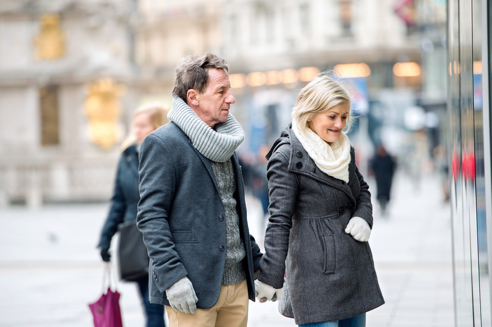 Beautiful senior couple window shopping in historical centre of the city of Vienna, Austria. Winter.