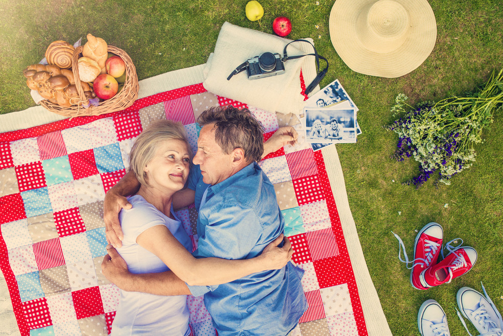 Beautiful senior woman and man lying on a colorful blanket