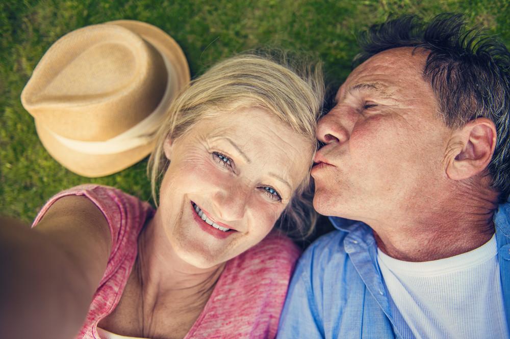Beautiful senior woman and man lying on the gras taking selfie