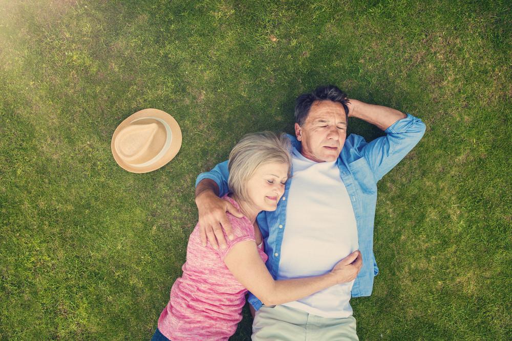 Beautiful senior woman and man lying on the gras
