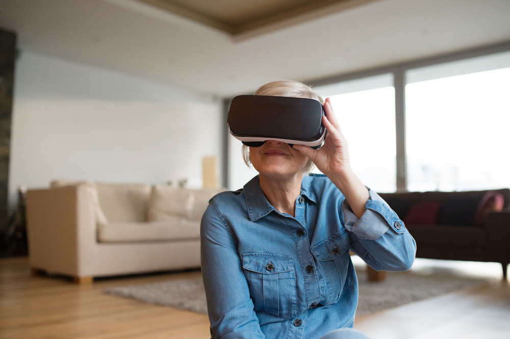 Beautiful senior woman in denim shirt at home in her living room wearing virtual reality goggles