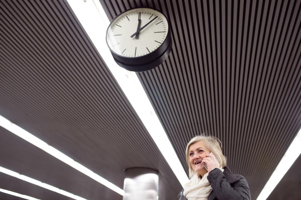 Beautiful senior woman standing at the underground platform, waiting, talking on the phone
