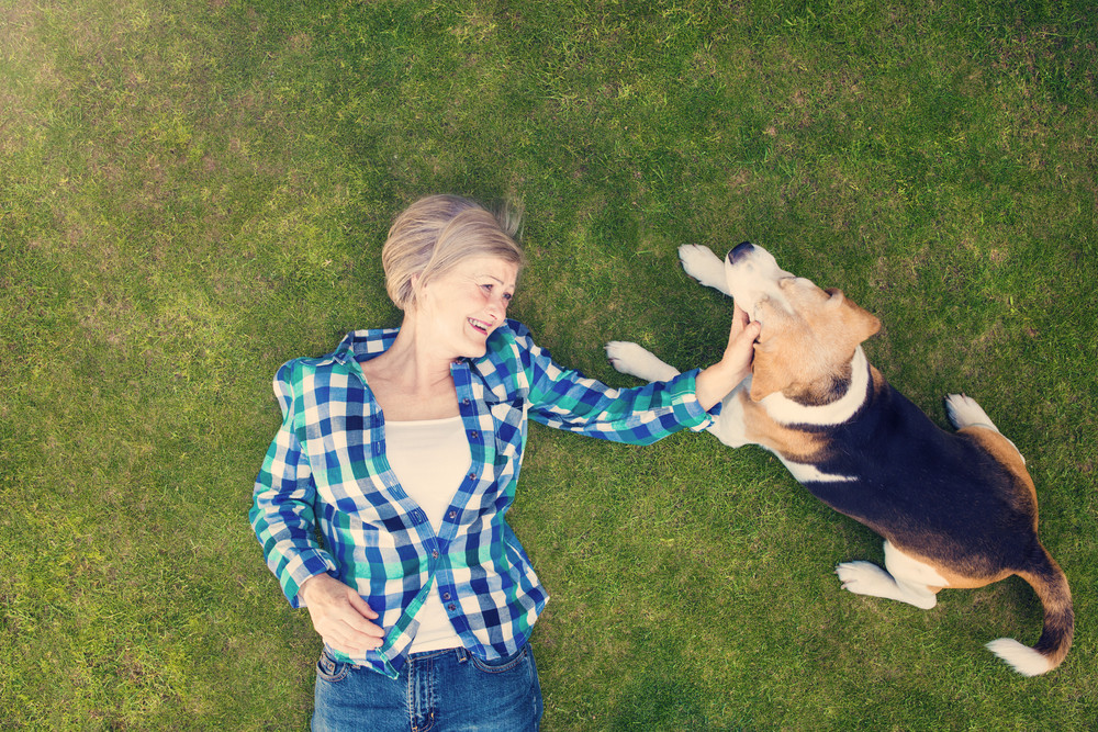 Beautiful senior woman with her dog lying on grass