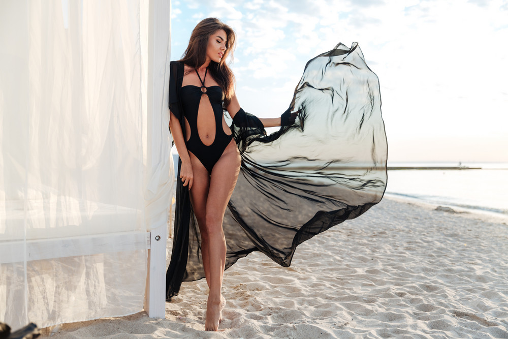 Beautiful slim brunette girl posing in swimsuit and black shawl near beach bed at the seashore