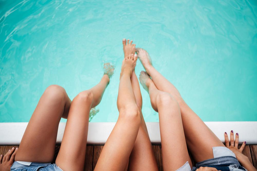 Beautiful slim legs of three young women in swimming pool
