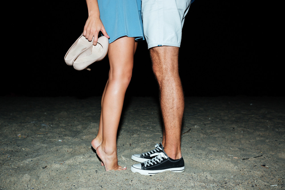 Beautiful slim legs of young couple standing on the beach at night