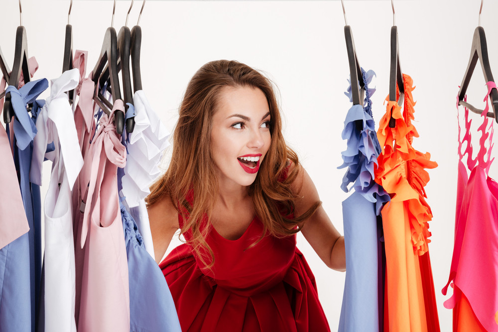 Beautiful smiling blonde woman standing inside wardrobe rack full of clothes looking away
