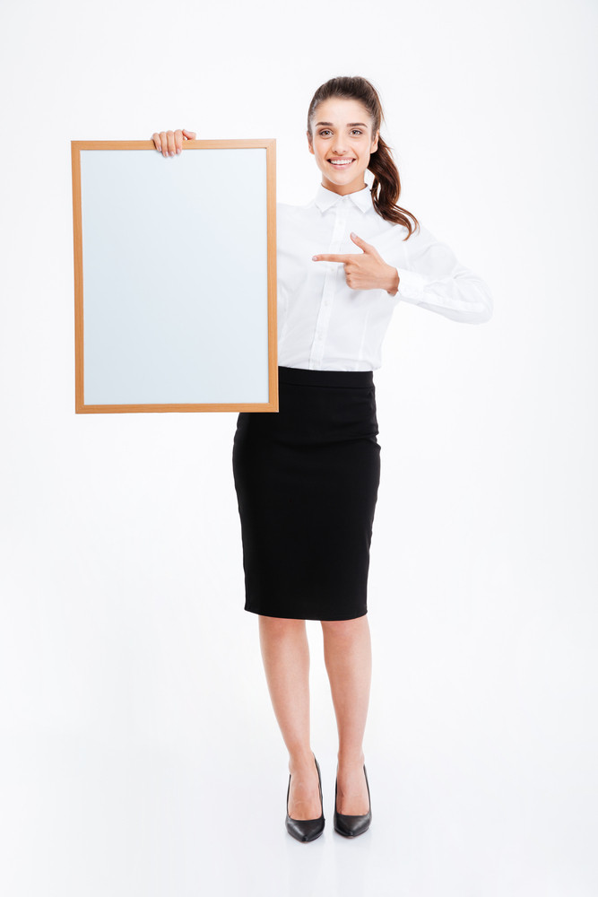 Beautiful smiling businesswoman pointing finger at blank board over white background