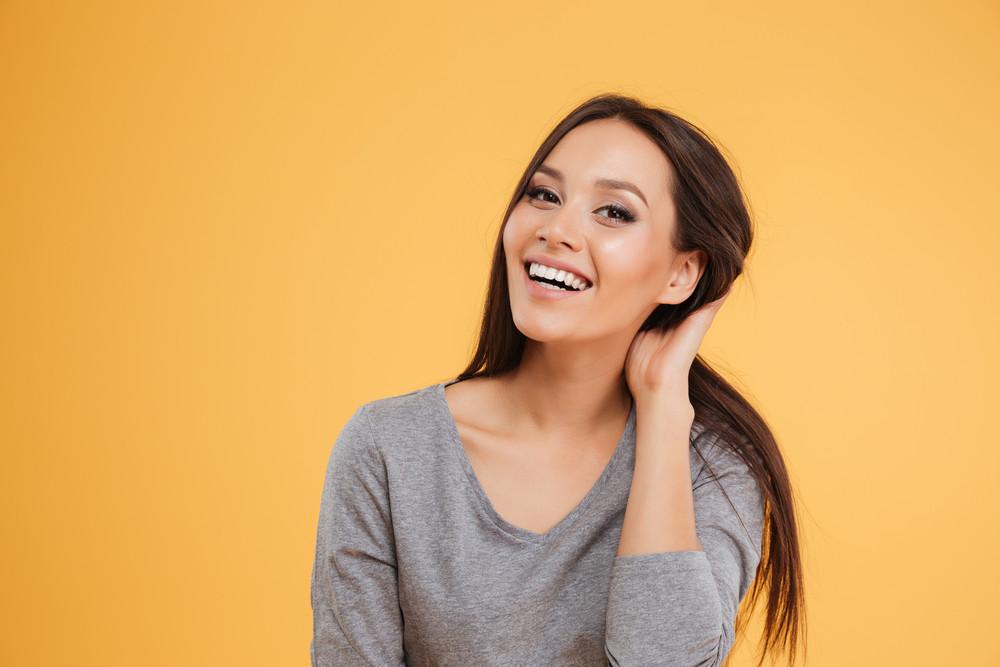 Beautiful smiling model in studio. isolated orange background
