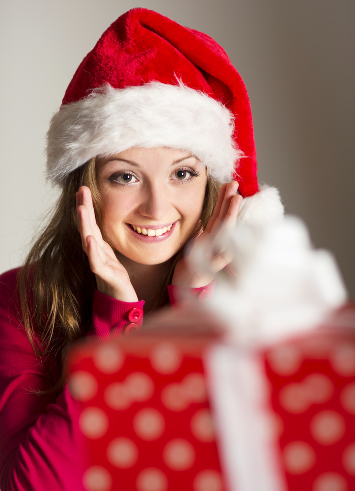 Beautiful smiling woman opening her christmas gift
