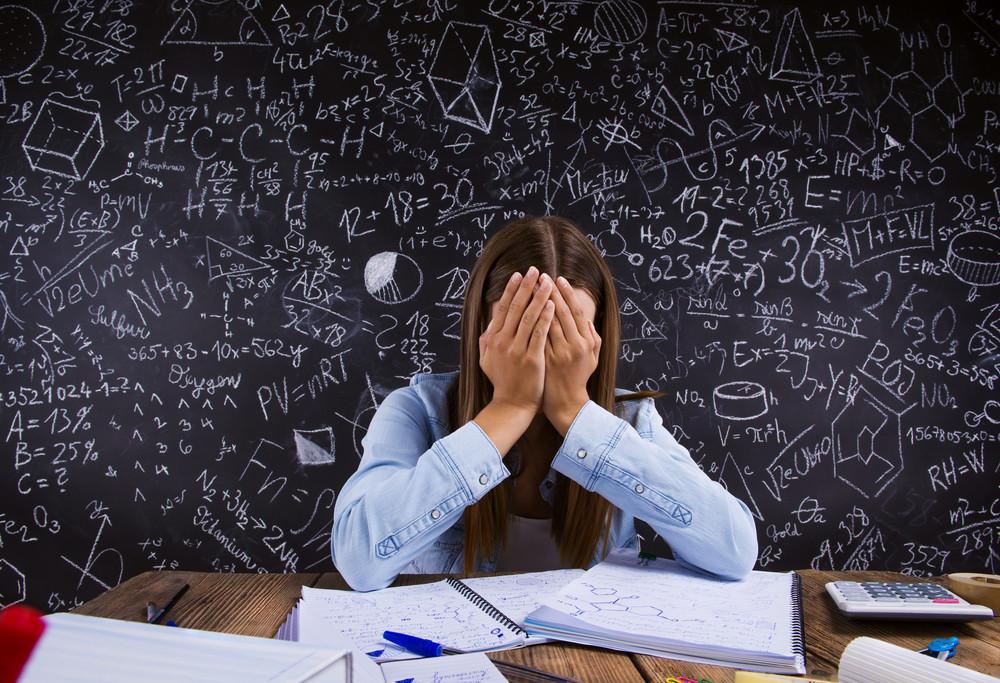 Beautiful student doing her homework in front of big blackboard