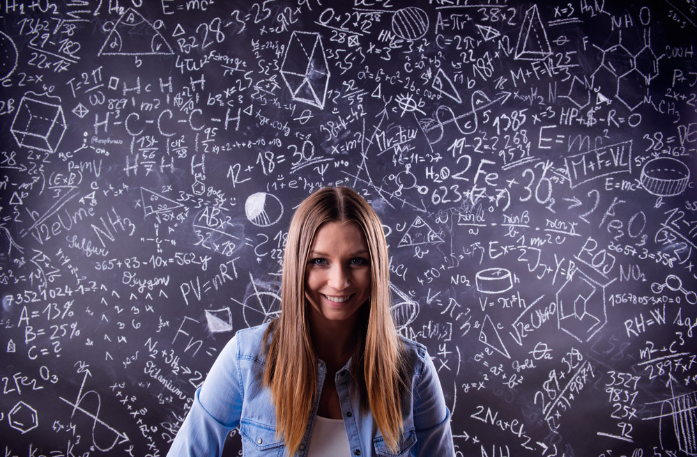 Beautiful student in blue denim shirt against big blackboard with mathematical symbols and formulas. Studio shot on black background.