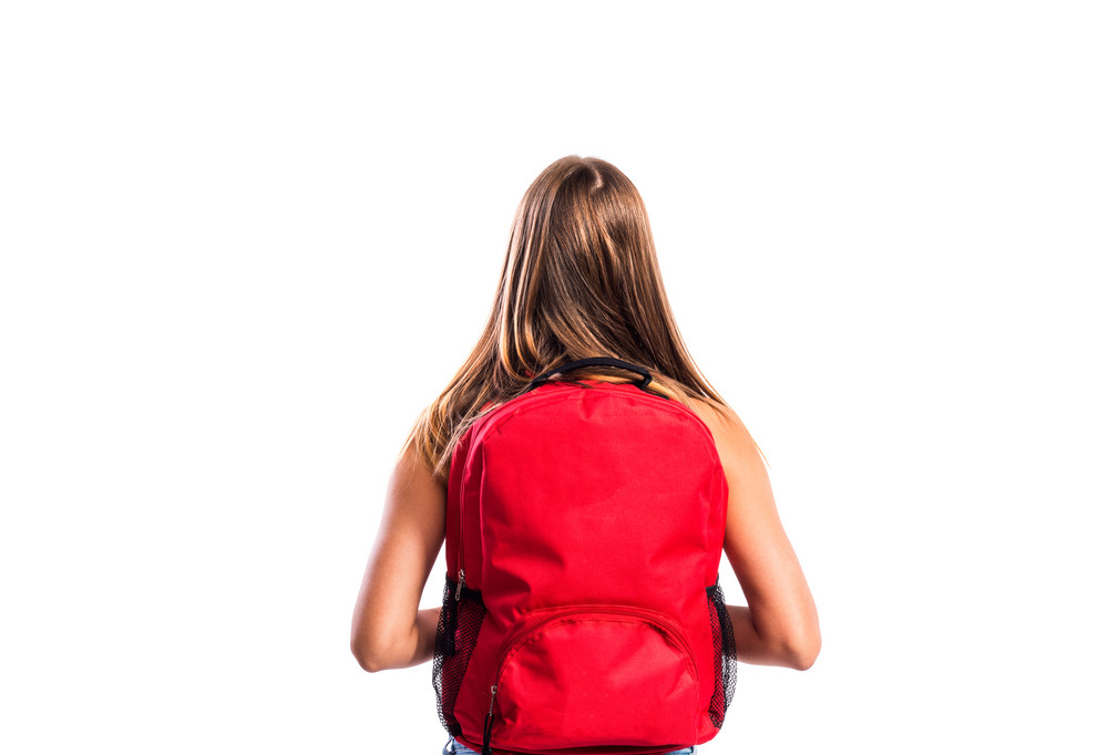 Beautiful student with red schoolbag. Studio shot on white background, isolated. Rear view.