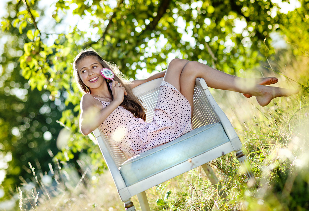 Beautiful teenage girl is enjoying leisure time with lollipop in green sunny park