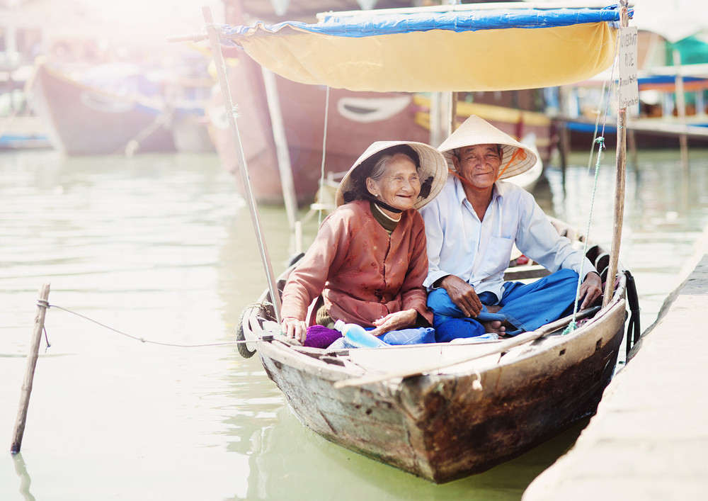 Beautiful vietnamese senior couple in a traditional boat