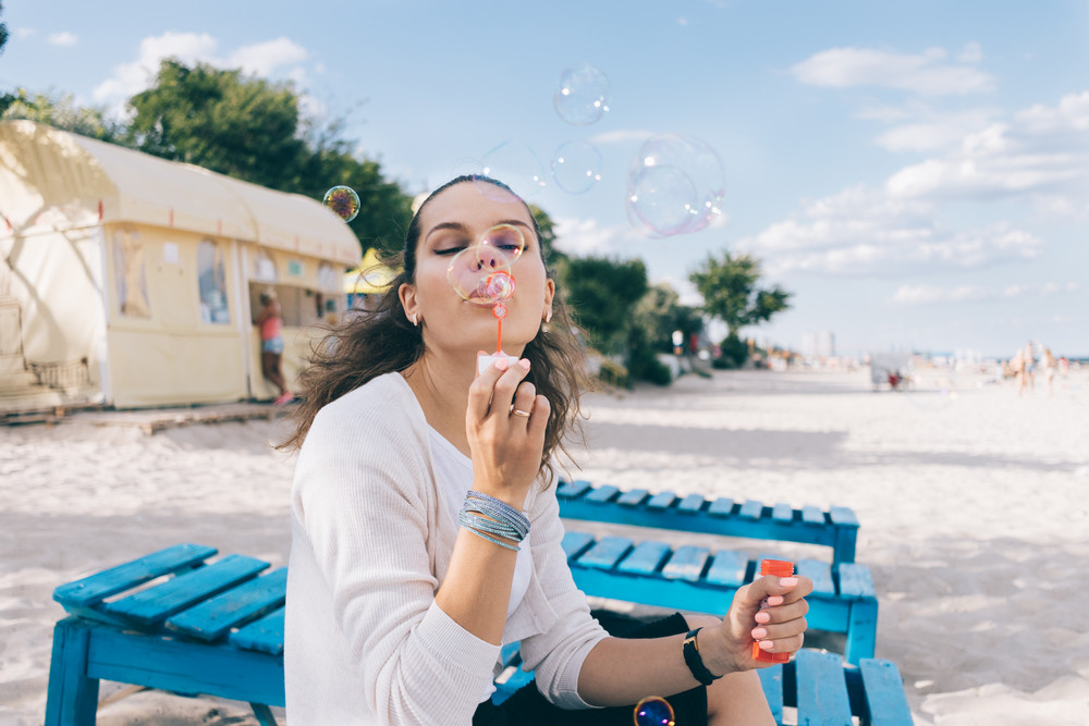 Beautiful woman and soap bubbles on the beach in summer