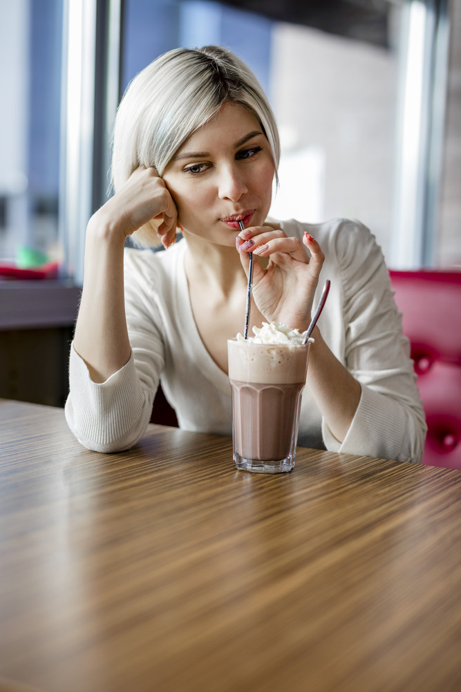 Beautiful Woman Drinking Hot Chocolate With Cream In Cafe