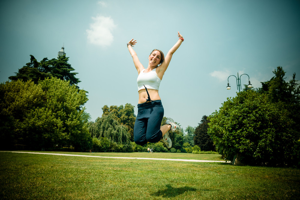 beautiful woman fitness jumping at the park