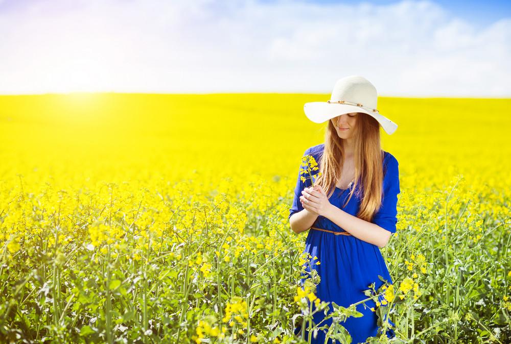 Beautiful woman in blue dress in summer canola field.