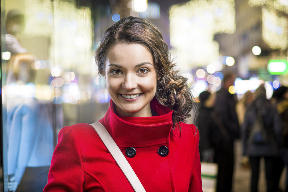 Beautiful woman in red coat outside in the winter night city