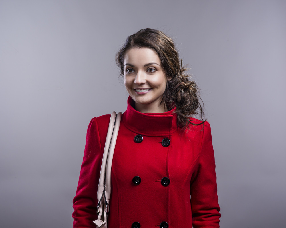 Beautiful woman in red coat. Studio shot on gray background ...