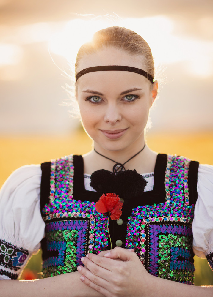 Beautiful woman in the field. She is wearing traditional Eastern Europe folk costumes.