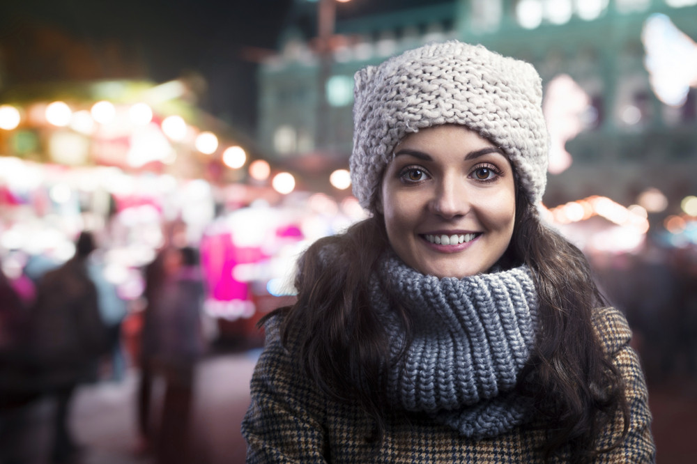 Beautiful woman in warm clothing outside in the winter night city