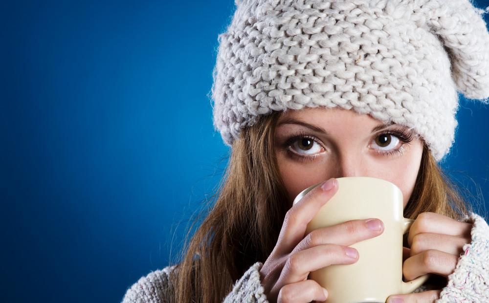 Beautiful woman in warm sweater on blue background