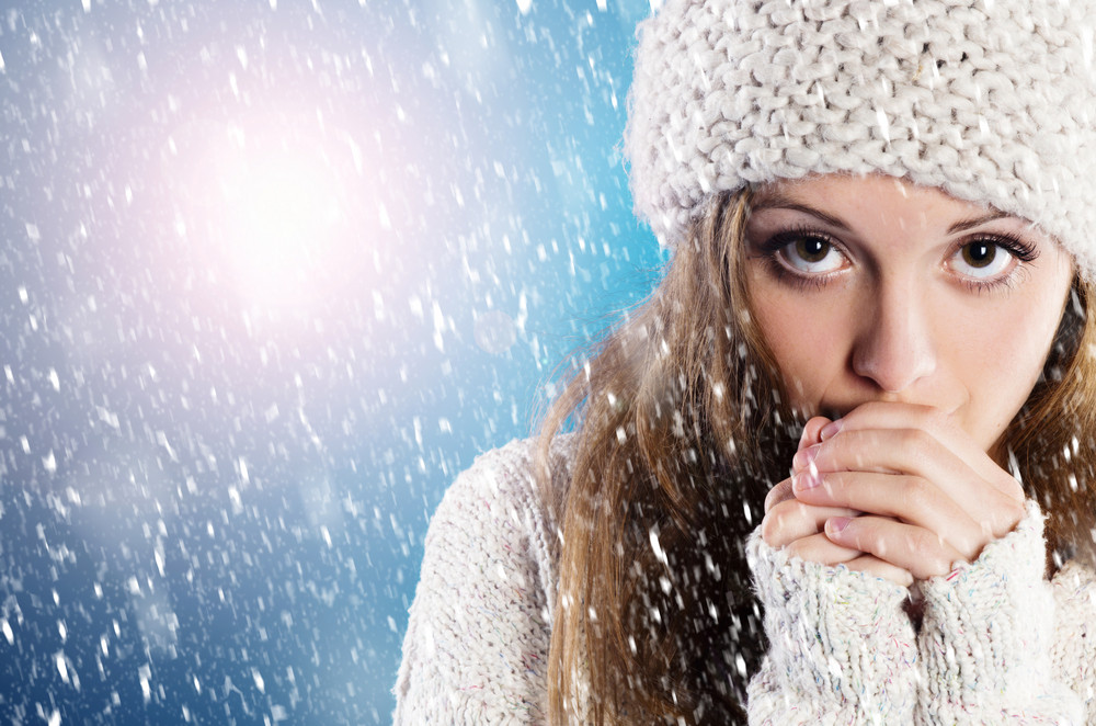 Beautiful woman in warm sweater with snowflakes around her, on blue background