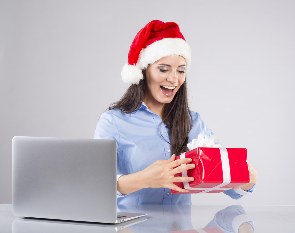 Beautiful woman is working in office with christmas hat